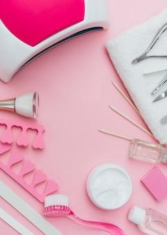 Herramientas de accesorios para el cuidado de las uñas sobre fondo rosa