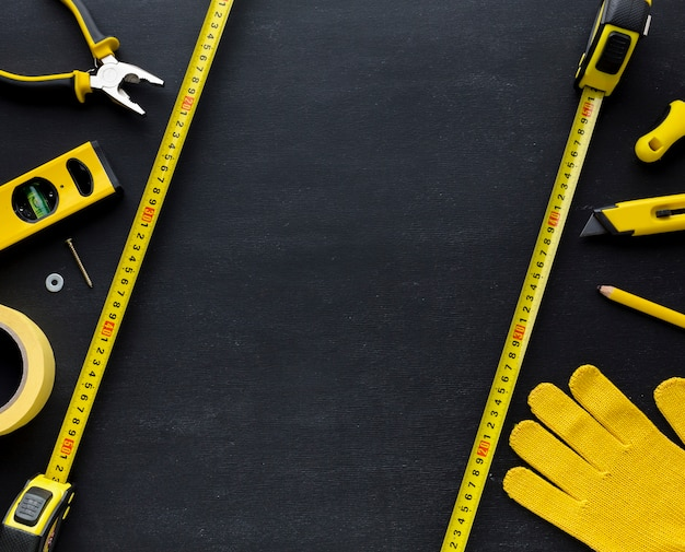Herramientas amarillas y guantes de construcción con espacio de copia