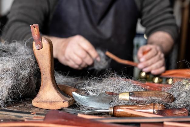 Herramientas de artesano de cuero en primer plano con un hombre trabajando detrás.