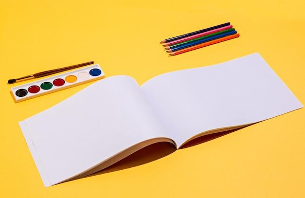 Herramientas artísticas: pinceles, pintura de acuarela, cuaderno