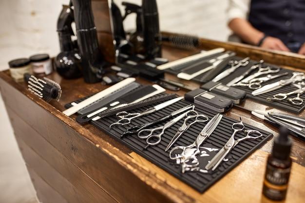 Herramientas de barbero en estante de madera y espejo en peluquería