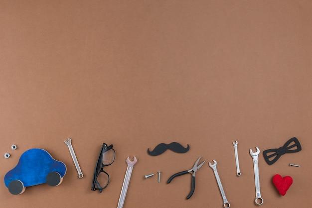 Herramientas con bigote de papel, gafas y coche de juguete.