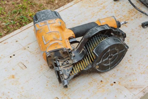 Herramientas de carpintería: pistola clavadora y lijadora en una mesa de trabajo