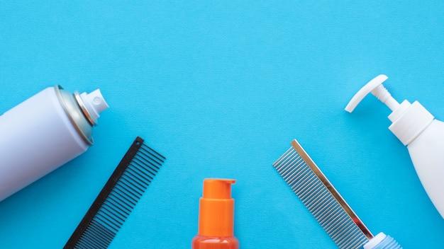 Herramientas clásicas de aseo y peluquería sobre una superficie azul: barniz, peines, lociones. vista superior, diseño, espacio de copia.