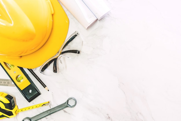 Herramientas de construcción con casco de seguridad sobre fondo de mármol blanco.
