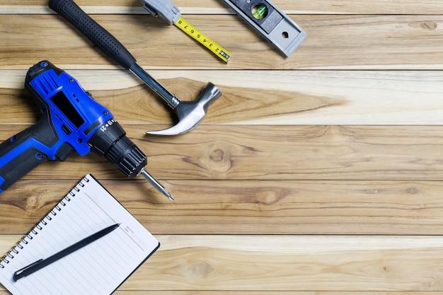 Herramientas de construcción y cuaderno en mesa de madera