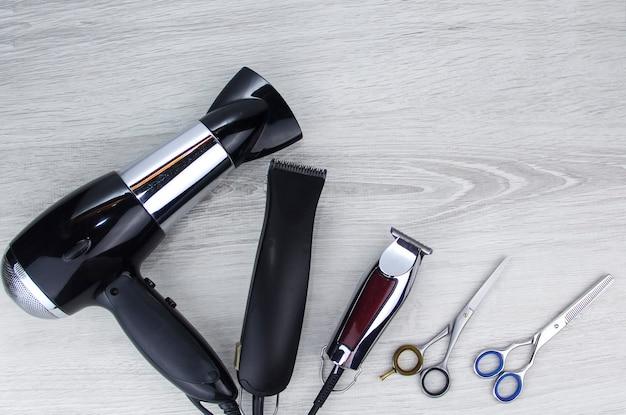 Las herramientas para cortar el cabello se encuentran sobre un fondo de madera. broche del pelo. broche del pelo.