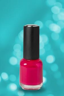 Herramientas cosméticas del arte de la manicura, botella de esmalte de uñas colorido rojo del gel en fondo azul del bokeh