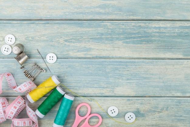 Herramientas para costura y costura sobre fondo de madera verde.