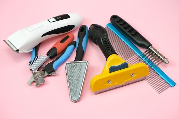 Herramientas de cuidado y aseo de mascotas sobre un fondo rosa. concepto de cuidado e higiene de mascotas