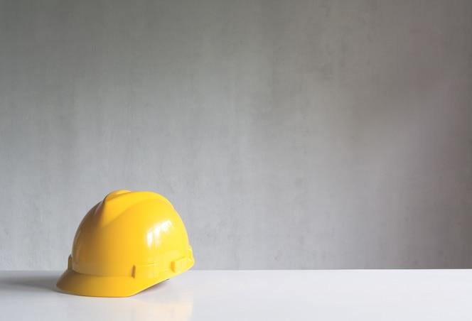 Herramientas de construcción o equipo de seguridad con casco amarillo en la mesa.