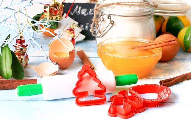 Herramientas de decoración navideña para hornear galletas forman un rodillo sobre un fondo de madera clara enfoque suave selectivo estilo rústico