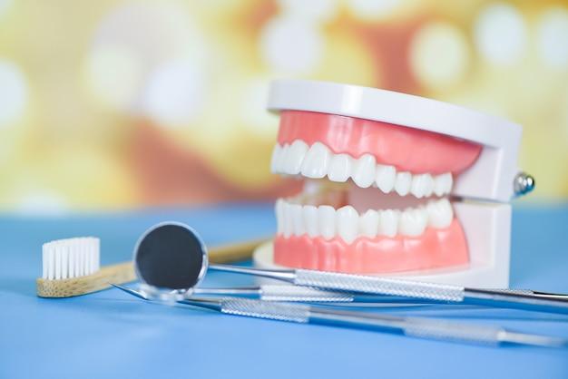 Herramientas de dentista con prótesis dentales de bambú instrumentos de odontología y concepto de chequeo de higienista dental