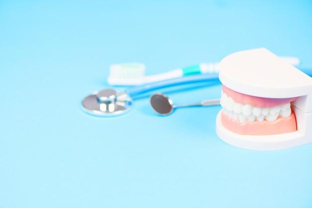 Herramientas de dentista con prótesis dentales instrumentos de odontología e higiene dental y chequeo de equipos con modelo de dientes y espejo bucal salud bucal / cuidado dental