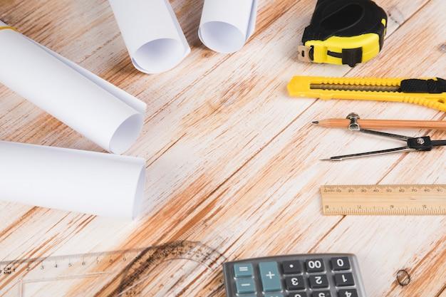 Herramientas para diseñar una casa en una mesa de madera.