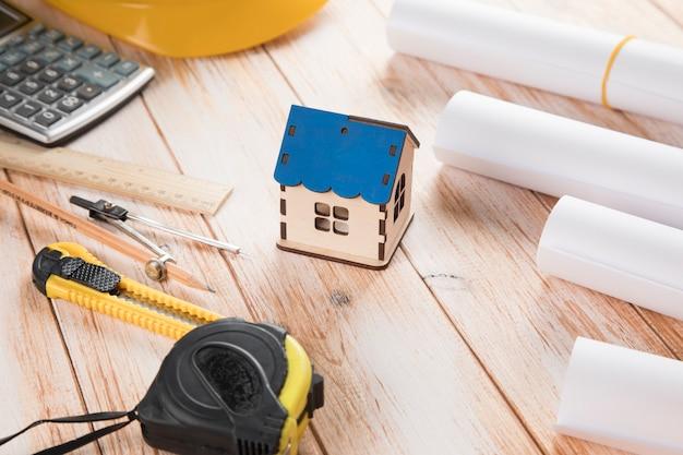 Herramientas de diseño y una pequeña casa en una mesa de madera.