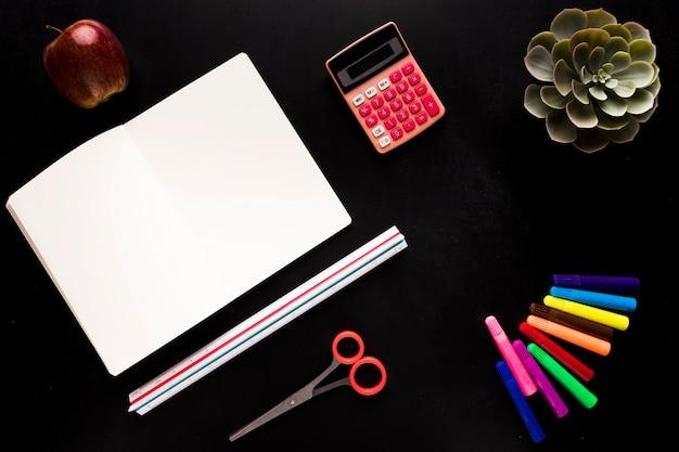 Herramientas escolares en mesa negra