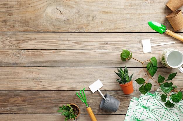 Herramientas de jardinería y flores en maceta sobre fondo de madera vintage