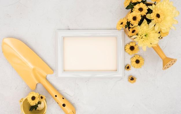 Herramientas de jardinería y flores con marco vacío