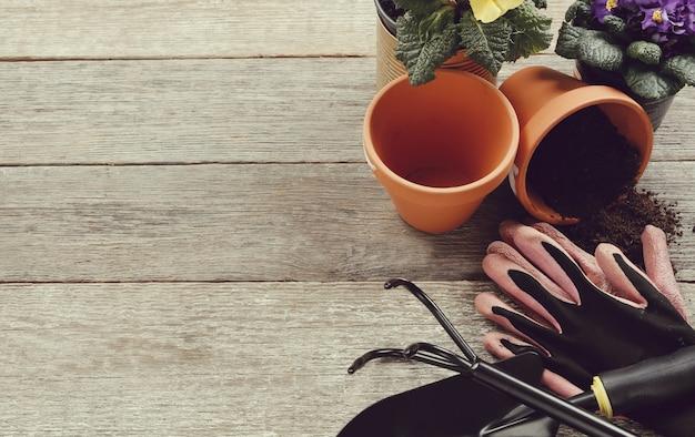 Herramientas de jardinería y maceta en mesa de madera