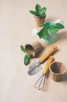 Herramientas de jardinería, macetas de papel, regaderas sobre papel artesanal.