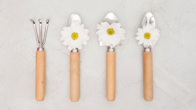 Herramientas de jardinería minimalistas y flores de margarita