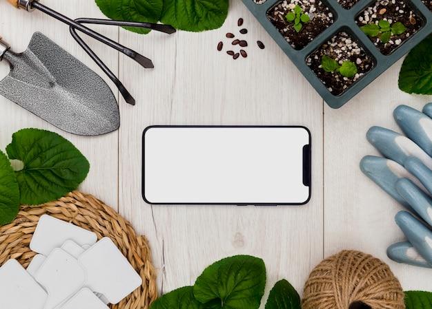 Herramientas de jardinería y plantas planas con teléfono en blanco