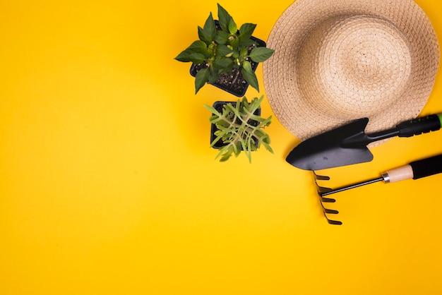 Herramientas de jardinería con sombrero de paja y espacio de copia