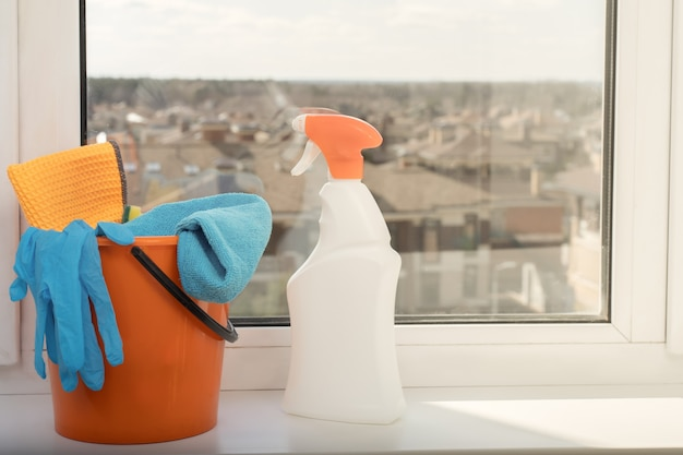 Herramientas de limpieza, balde, guantes junto a una ventana.