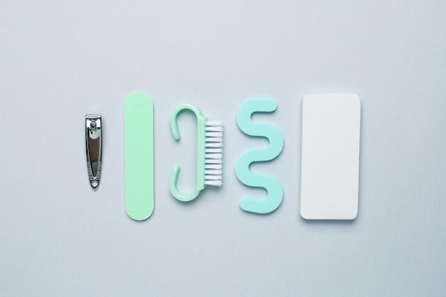 Herramientas de manicura pedicura, lima de uñas, tijeras de pedicura y separador para los dedos sobre fondo azul.