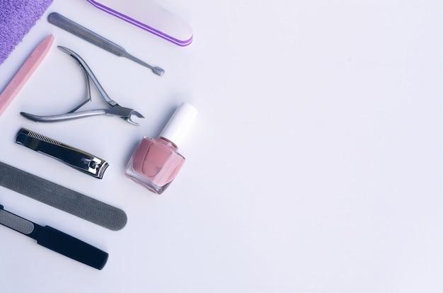 Herramientas de manicura y pedicura utilizadas en salones y salones de belleza. lima de uñas, quita cutículas, tampones, cortaúñas y cortador de bordes, cortador de alicates, empujador de uñas y esmalte de uñas desnudo. copia espacio