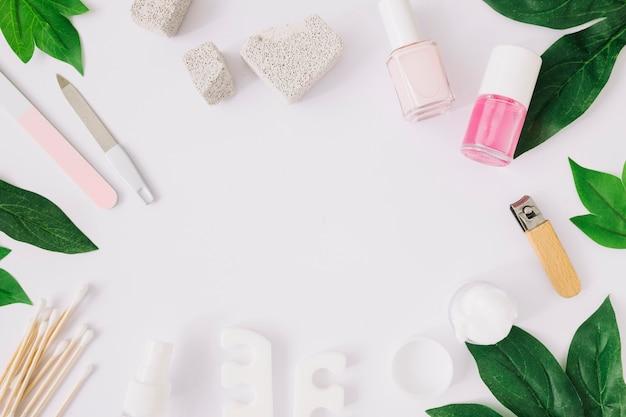 Herramientas de manicura y productos con hojas verdes sobre superficie blanca.