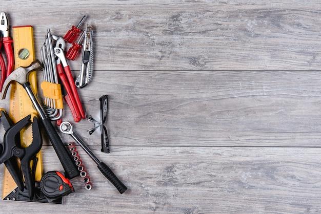 Herramientas manuales de construcción en plano sobre fondo de madera