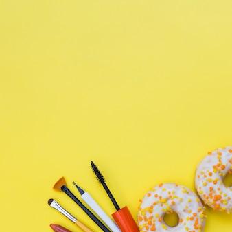 Herramientas de maquillaje y dos rosquillas en fondo amarillo