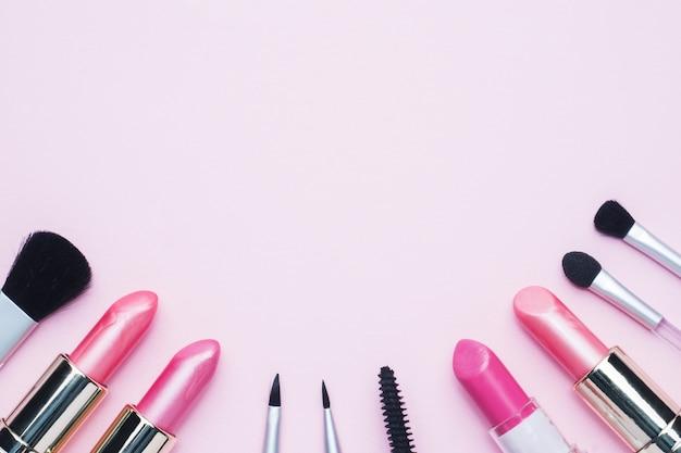 Herramientas de maquillaje profesional. el lápiz labial de los cepillos se ruboriza sombra de ojos en un fondo en colores pastel rosado con el espacio de la copia. lay flat