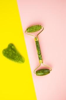 Herramientas de masaje facial green gua sha. rodillo de jade de cuarzo verde sobre fondo rosa y amarillo. cuidado anti-edad, lifting y tonificante en casa. copie el espacio.