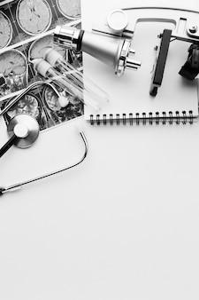 Herramientas médicas en blanco y negro y bloc de notas con espacio de copia