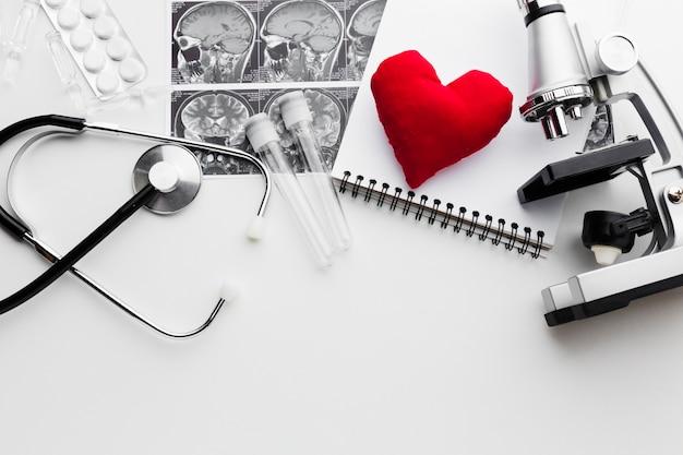 Herramientas médicas en blanco y negro y corazón rojo
