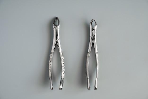 Herramientas médicas de odontología forcept superior / inferior sobre fondo gris.