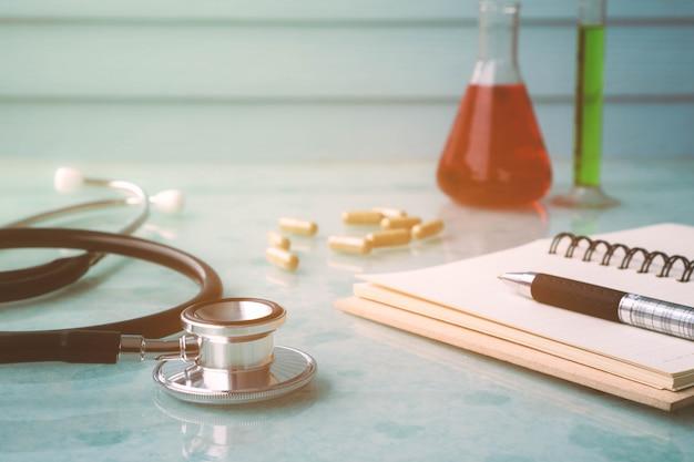 Herramientas de médico para una buena salud con estetoscopio, cuaderno, pluma, medicina y tubo de ensayo.