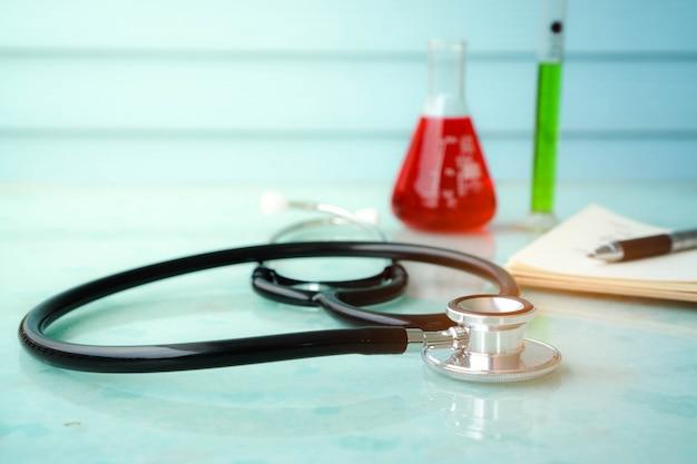 Herramientas de médico para una buena salud con estetoscopio, cuaderno y probeta.