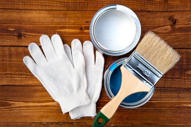 Herramientas necesarias para un trabajo de pintura: pincel, cubo de pintura, guantes protectores sobre tablas de madera