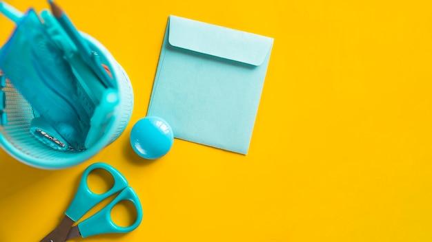 Herramientas de oficina azul en taza en superficie amarilla