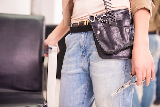 Herramientas de peluquería cuidadosamente guardadas en un cinturón de cuero.