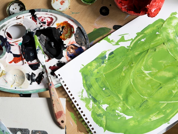 Herramientas de pintura desordenadas junto a pintura verde.