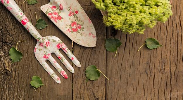 Herramientas y plantas en mesa de madera con espacio de copia