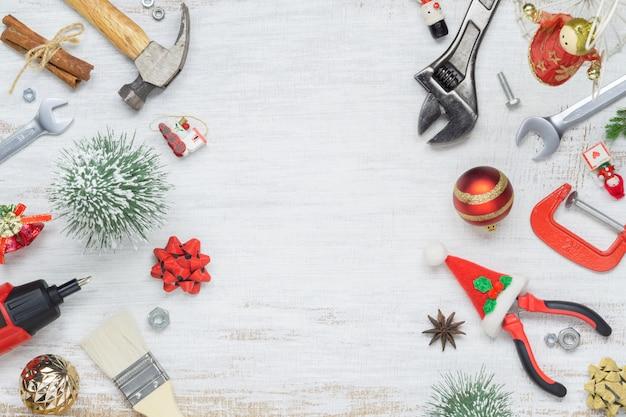 Herramientas prácticas de construcción con adornos navideños en madera blanca