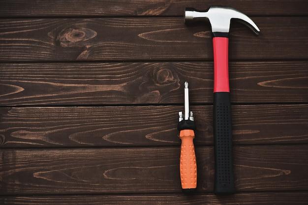 Herramientas de primer plano como martillo y destornillador en una mesa de madera