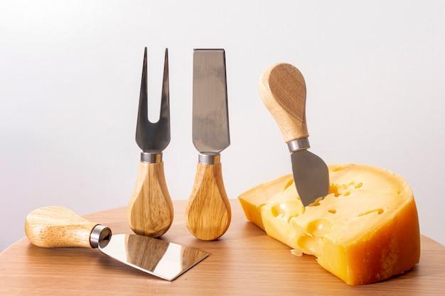 Herramientas de primer plano con una rodaja de queso sobre una mesa