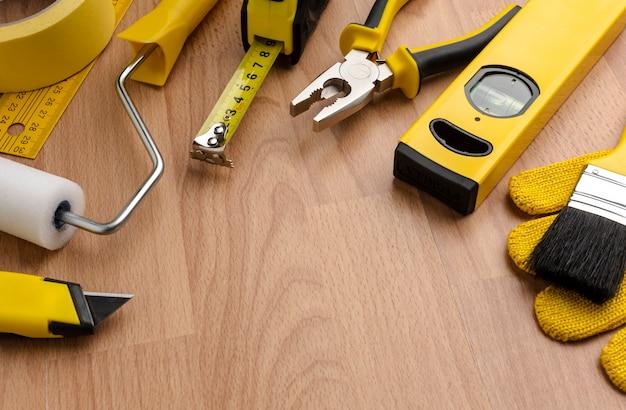 Herramientas de reparación amarillo de alta vista sobre fondo de madera